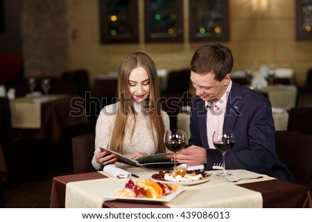 Cheerful couple with menu in a restaurant. - stock photo