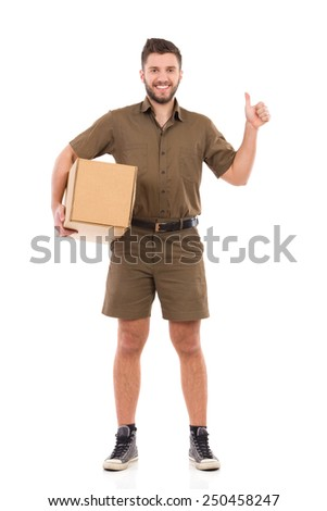 Cheerful courier standing with a carton box under his arm and showing thumb up. Full length studio shot isolated on white. - stock photo