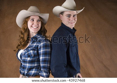 Cheerful Cowboy and Cowgirl couple in studio - stock photo