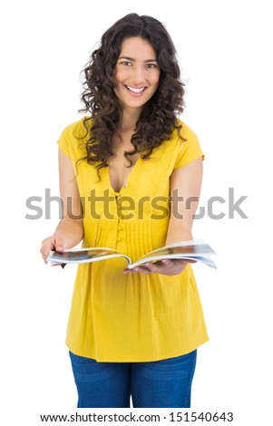 Cheerful curly haired brunette on white background reading magazine - stock photo
