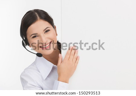 Cheerful customer service representative. Cheerful young female customer service representative in headset looking out of the poster while isolated on white - stock photo