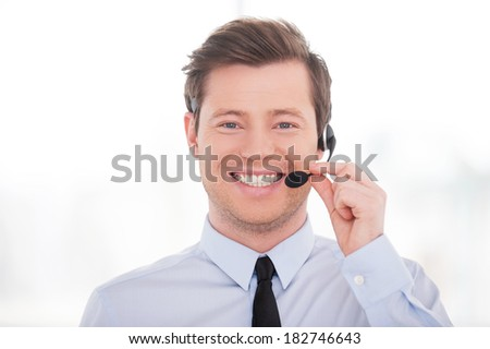 Cheerful customer service representative. Handsome young man in shirt and tie adjusting his headset and smiling at camera  - stock photo