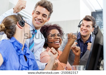 Cheerful customer service representatives and manager celebrating success at desk in office - stock photo