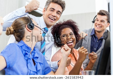 Cheerful customer service representatives and manager celebrating success in call center - stock photo