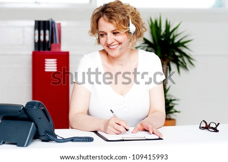 Cheerful customer support executive at work writing down customer complaints - stock photo