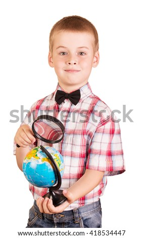 Cheerful, cute schoolboy holding a magnifying glass and globe isolated on white background. - stock photo