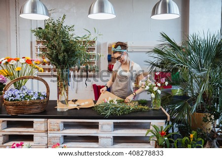 Cheerful cute young woman florist enjoying creating bouquet in flower shop - stock photo