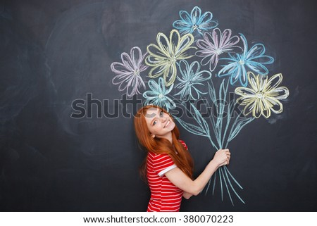 Cheerful cute young woman posing with bouquet of flowers drawn on blackboard background - stock photo