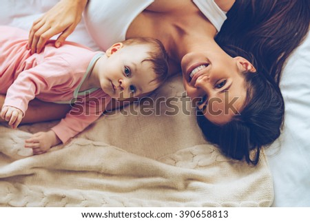 Cheerful cuties. Top view of cheerful beautiful young woman looking at camera with smile while lying in bed with her baby girl - stock photo