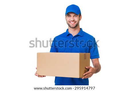Cheerful delivery man. Happy young courier holding a cardboard box and smiling while standing against white background - stock photo