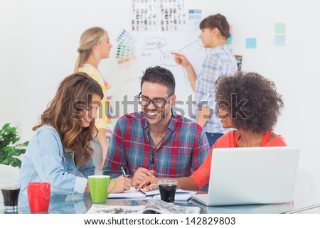 Cheerful designers brainstorming together in their office - stock photo