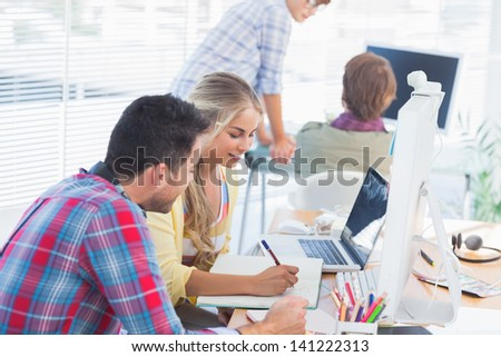 Cheerful designers working on a document with colleagues discussing behind - stock photo