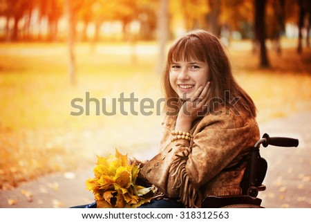 cheerful disabled girl in wheelchair in the autumn park - stock photo