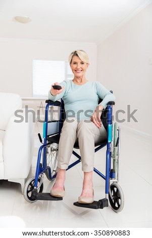 cheerful disabled senior woman watching television in living room - stock photo