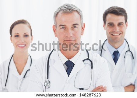 Cheerful doctors posing together crossing arms in bright office - stock photo