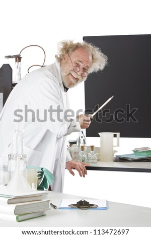 Cheerful eccentric senior scientist in his lab points to blackboard and explains his ideas. High key, vertical, copy space. - stock photo