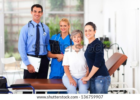 cheerful elderly patient and her daughter in hospital with doctor and nurse - stock photo