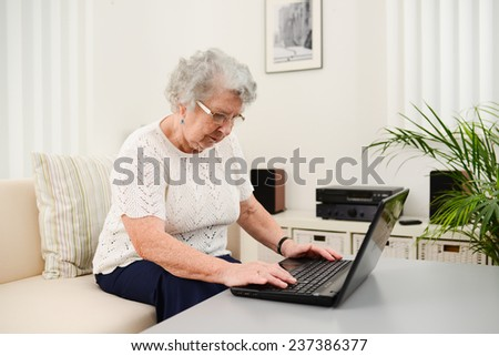 cheerful elderly woman web surfing and shopping on internet at home with laptop  - stock photo