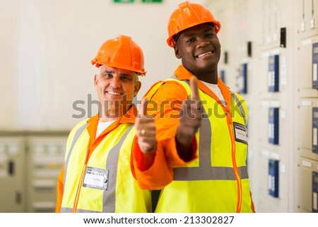 cheerful electrical engineers giving thumbs up - stock photo