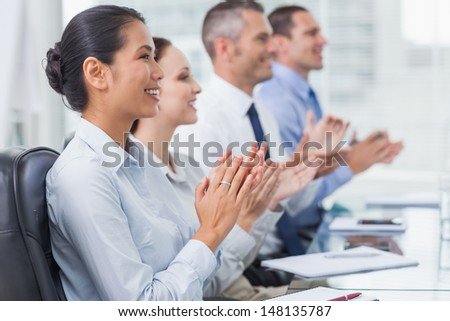 Cheerful employees in bright office applauding for presentation - stock photo