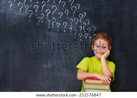 Cheerful encoureged primary school age boy have a lot of question after reading a pile of books - stock photo
