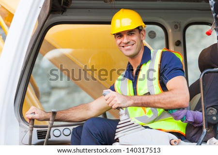cheerful excavator operator on construction site - stock photo