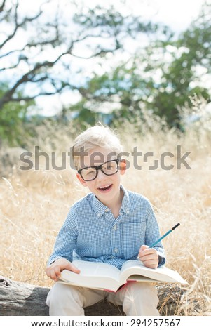 cheerful excited little boy studying with book and pencil ready for school, back to school concept - stock photo