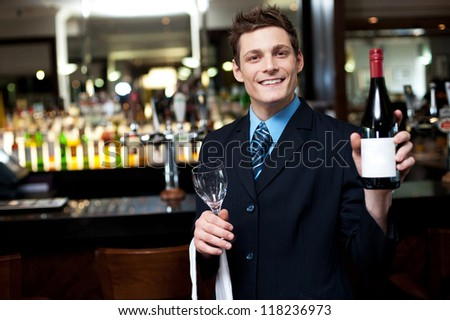 Cheerful executive posing with a bottle of wine. Bar in the background - stock photo