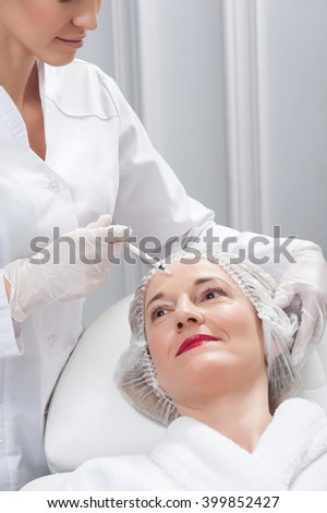 Cheerful expert beautician is serving her patient - stock photo