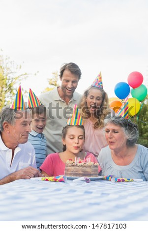 Cheerful extended family blowing out birthday candles together outside at picnic table - stock photo