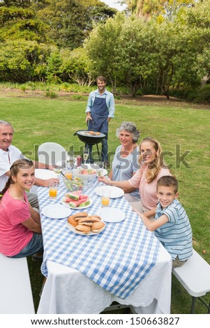 Cheerful extended family having a barbecue outside smiling at camera - stock photo