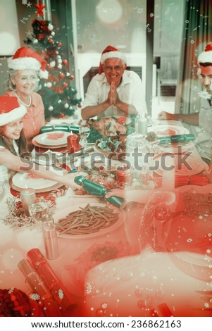 Cheerful family at dining table for christmas dinner against candle burning against festive background - stock photo
