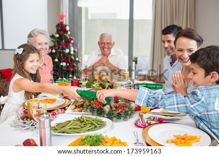 Cheerful family at dining table for christmas dinner in the house - stock photo