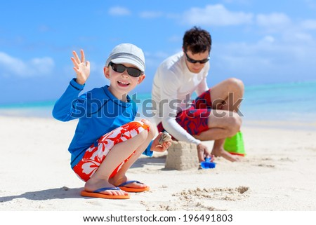 cheerful family building sand castle at the beach - stock photo