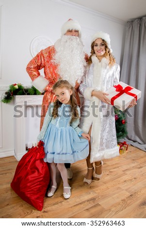 Cheerful family celebrating Christmas. Russian traditions. Father Frost and maiden Snow. - stock photo