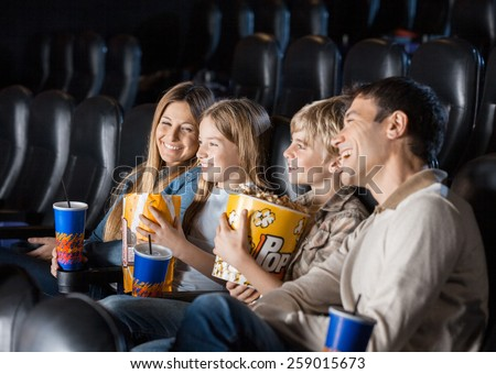 Cheerful family having snacks while enjoying movie in cinema theater - stock photo