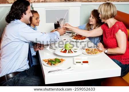 Cheerful family in a cafe clinking their glasses - stock photo