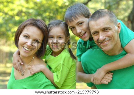 Cheerful family in green shirts walking in the summer park - stock photo