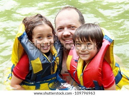 Cheerful family in the water wearing life vest smiling at camera - stock photo