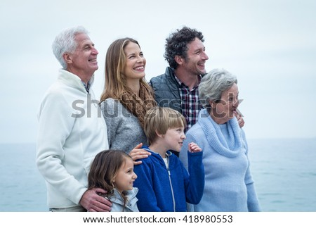 Cheerful family looking away at beach against sky - stock photo