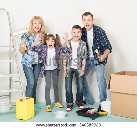 Cheerful family makes repairs at home. Happy mother, father, son and daughter - painting wall at room - stock photo