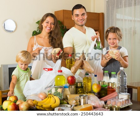 Cheerful family of four with bags of  products at home - stock photo