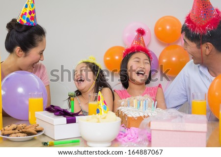 Cheerful family of four with cake and gifts at a birthday party - stock photo