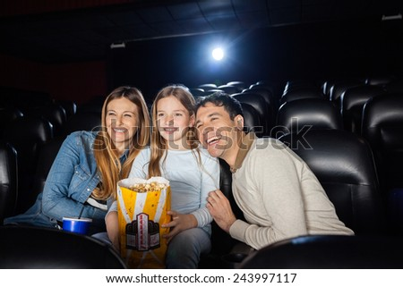 cheerful family of three enjoying film in movie theater - stock photo
