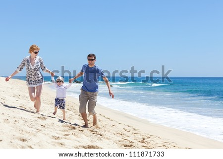 cheerful family of three running at the beach - stock photo