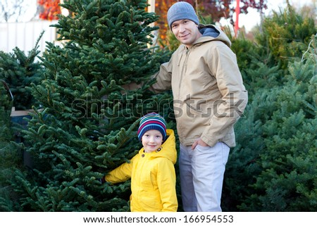 cheerful family of two buying christmas tree together - stock photo
