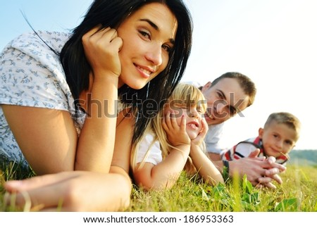 Cheerful family on beautiful summer meadow enjoying and having fun - stock photo