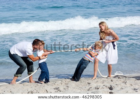 Cheerful family playing tug of war at the beach - stock photo