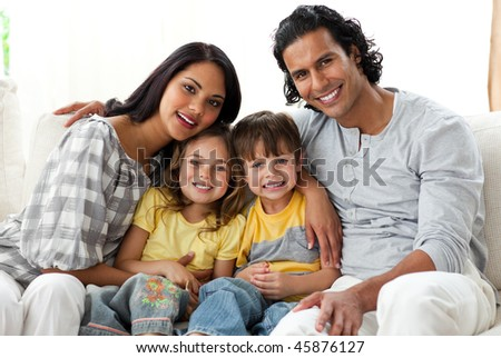 Cheerful family relaxing sitting on a sofa in their living room - stock photo