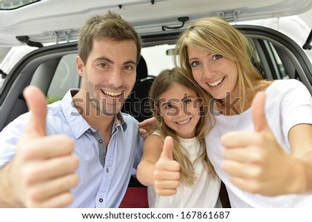 Cheerful family showing thumbs up - stock photo